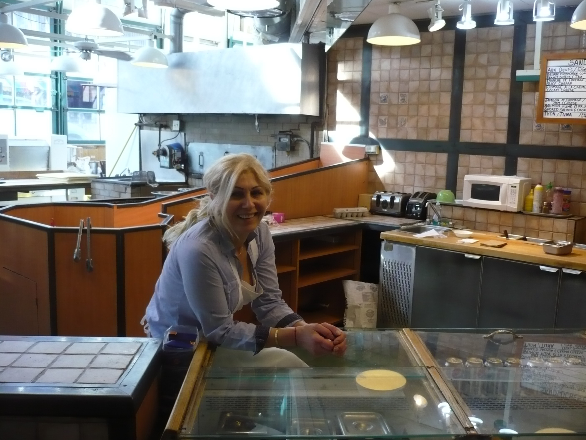 owner of place bagel du faubourg standing at counter in front of oven