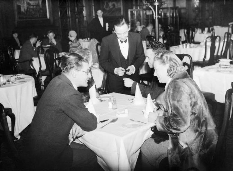A_group_of_diners_give_their_order_to_the_waiter_at_a_restaurant_in_the_West_End_of_London,_spring_1941._D2957